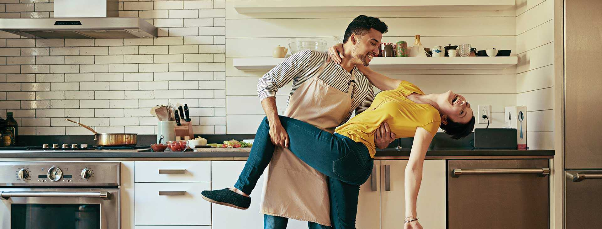 Young couple dancing and smiling with delight while cooking in their new kitchen