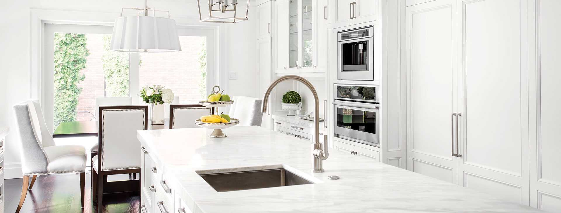 Open-plan kitchen redesign, with accents of silver hardware and refined white stone bench top