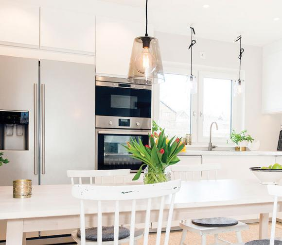 Modern white family kitchen with stainless steel appliances